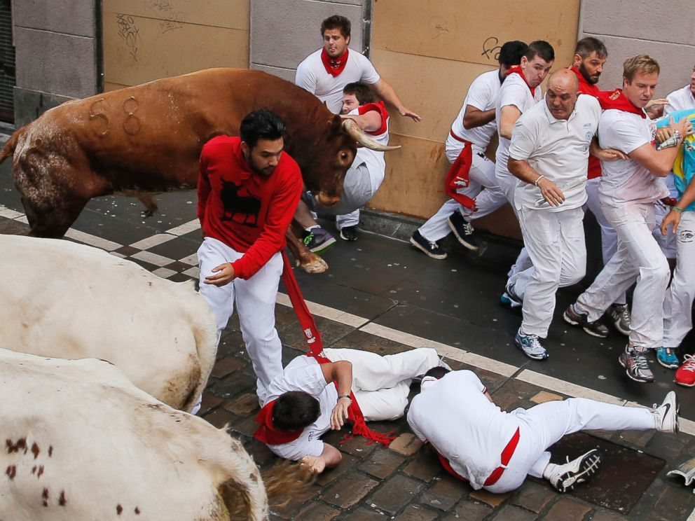 PHOTO: A reveler is tossed by a Miura fighting bull as other fall during the running of the bulls at the San Fermin festival, in Pamplona, Spain, on July 14, 2014.