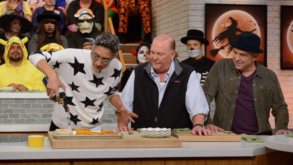 """Carla Hall, Mario Batali, and Michael Symon shown on """"The Chews Halloween Bash"""" which aired on October 31, 2017on ABC."""