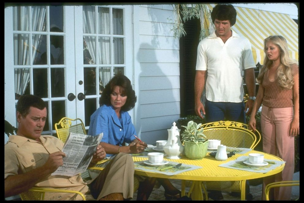 PHOTO: Larry Hagman (left) (as JR Ewing), Linda Gray (as Sue Ellen Ewing), Patrick Duffy (as Bobby Ewing), and Charlene Tilton (as Lucy Ewing) listen in an unidentified episode of the television series Dallas, 1979.