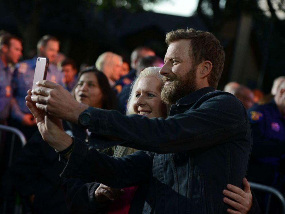 PHOTO: Country music star Dierks Bentley poses with a neighbor during the block party in Austin, Texas, Oct. 17, 2017.