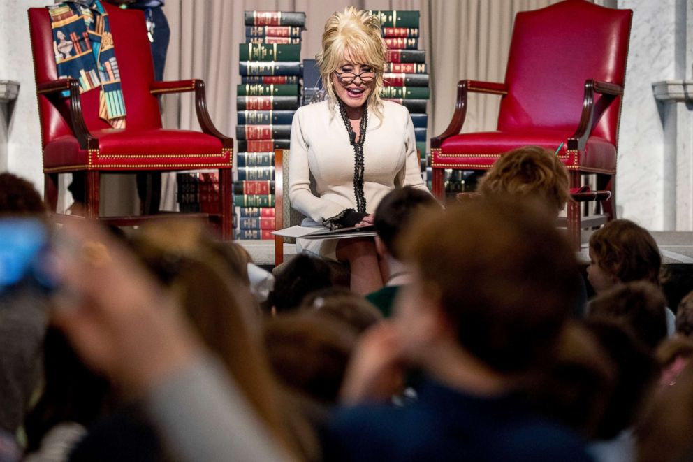 PHOTO: Dolly Parton reads her book Coat of Many Colors, to children as she makes it the 100 millionth book that Imagination Library donates to the Library of Congress collection at the Library of Congress, Feb. 27, 2018, in Washington.