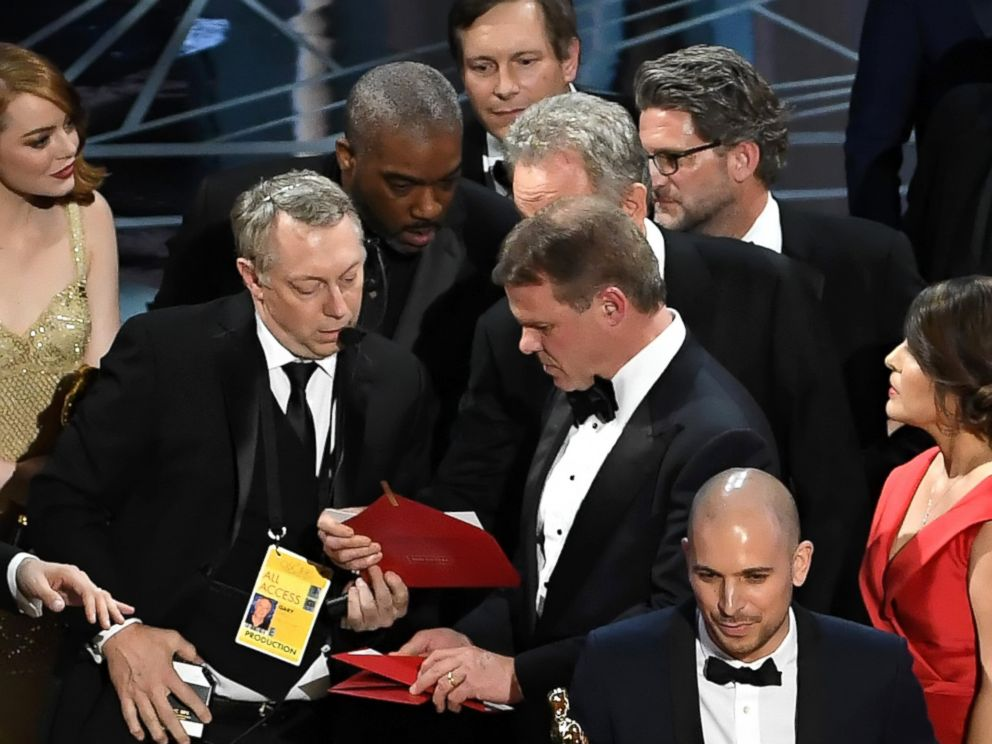 PHOTO: La La Land producer Fred Berger, bottom, speaks at the microphone as production staff consult behind him regarding a presentation error of the Best Picture award during the 89th Annual Academy Awards on Feb. 26, 2017 in Los Angeles.
