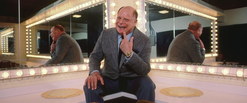 PHOTO: Comedian Don Rickles laughs while sitting on the counter in a mirrored dressing room.