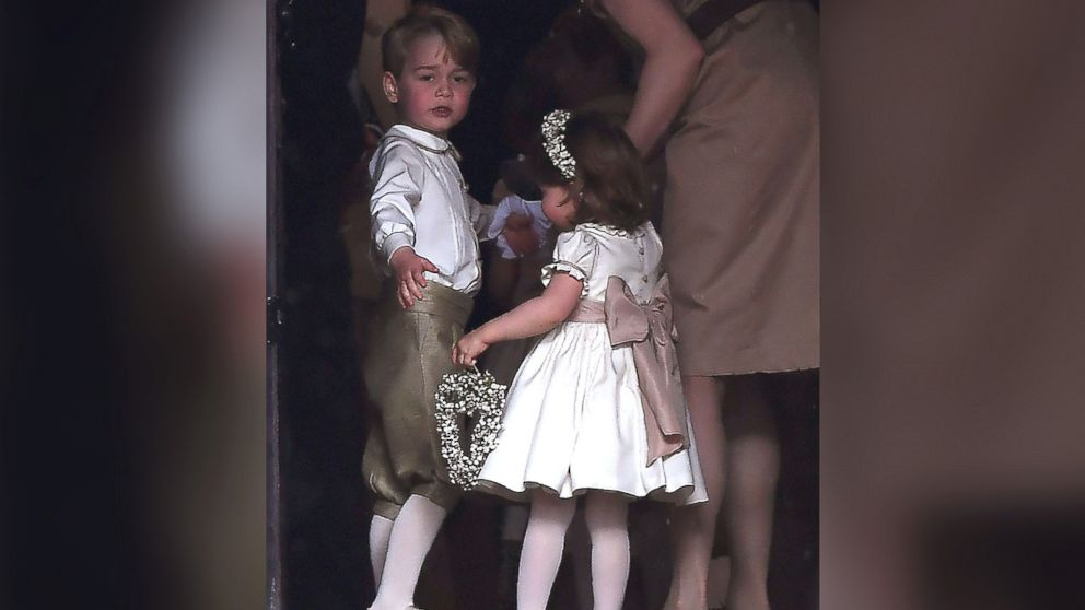 Britain's prince George, a pageboy, and princess Charlotte, a bridesmaid, stand with their nanny as they attend the wedding of their aunt Pippa Middleton to James Matthews at St Mark's Church in Englefield, west of London, May 20, 2017.