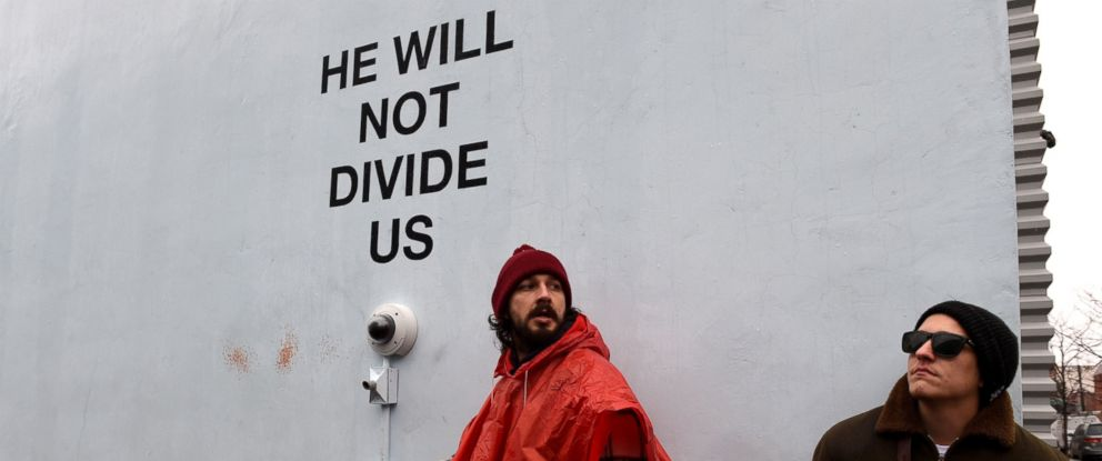 "PHOTO: Shia LaBeouf(L)is seen during his ""He Will Not Divide Us"" livestream outside the Museum of the Moving Image in Astoria, in the Queens borough of New York, Jan. 24, 2017 as a protest against President Donald Trump."