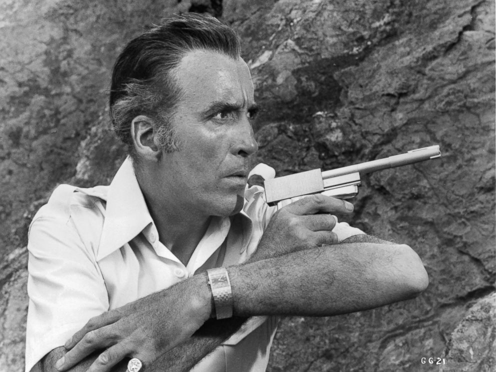 PHOTO: Christopher Lee along side a cliff wall pointing a gun in a scene from the film The Man With The Golden Gun, 1974.