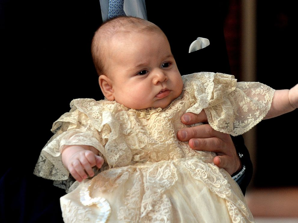 PHOTO: Britains Prince William, Duke of Cambridge holds his son, Prince George of Cambridge, as he arrives at Chapel Royal in St Jamess Palace in central London for the christening of the three month-old baby on October 23, 2013.