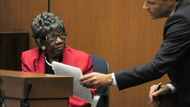 PHOTO: Deputy District Attorney David Walgren hands Ruby Mosley, character witness and former patient of Dr. Conrad Murray, a statement during her testimony.