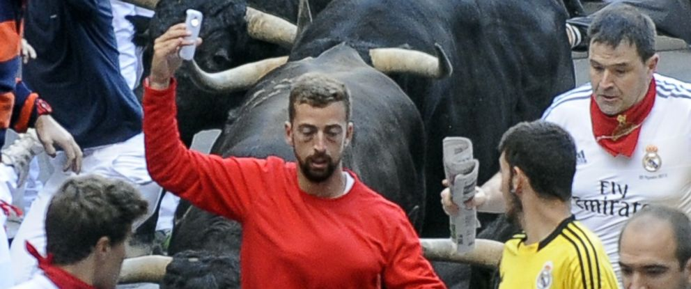 "PHOTO: A participant runs in front of Jandillas bulls as he takes a ""selfie"" during the fifth bull-run of the San Fermin Festival in Pamplona, northern Spain, on July 11, 2014."