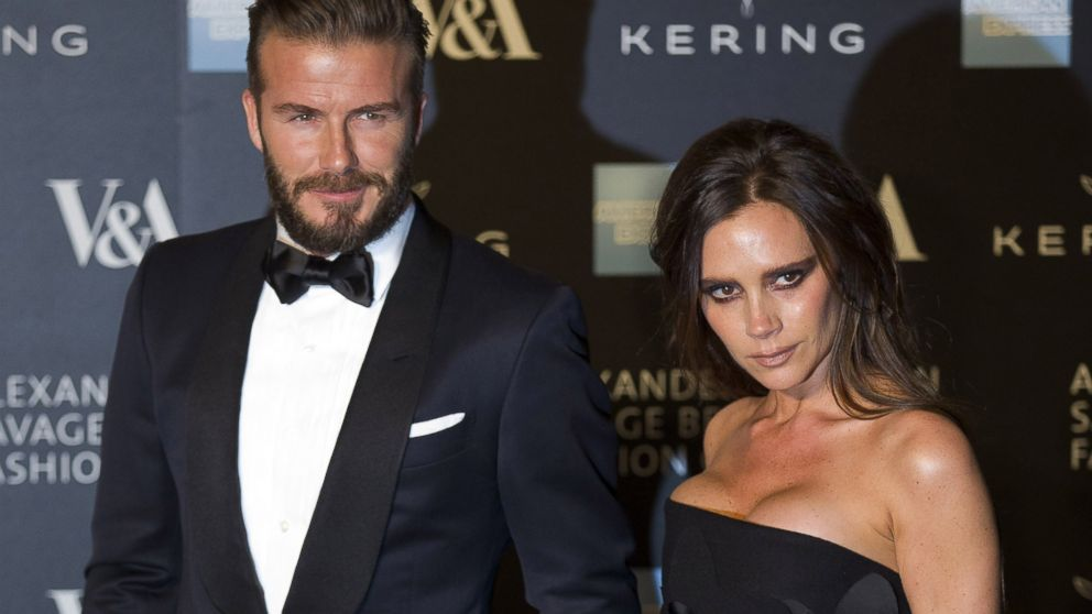 David Beckham and Victoria Beckham pose for pictures as they arrive on the red carpet for the 'Alexander McQueen: Savage Beauty Gala' at the Victorian & Albert Museum in London on March 12, 2015.