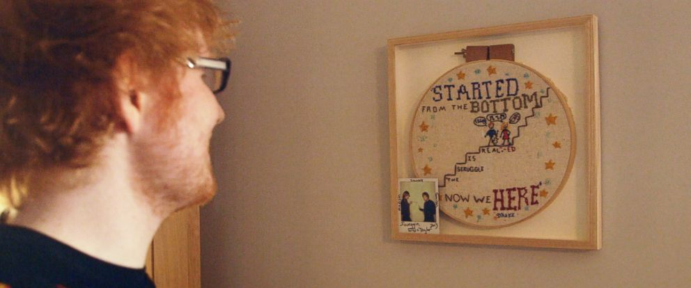 "PHOTO: Ed Sheeran shows off a needlepoint that was given to him by Taylor Swift on the MTV show, ""Nine Days and Nights of Ed Sheeran""."