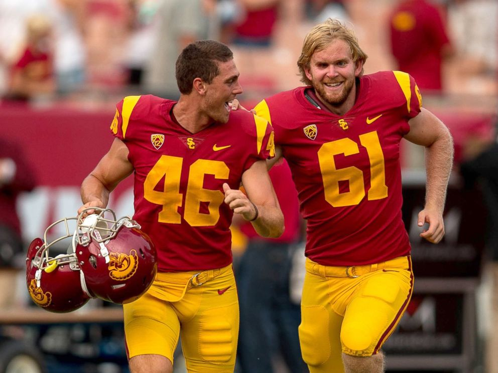 PHOTO: USC long snapper, Jake Olson, right, who has been blind since the age of 12, runs off the field with teammate Wyatt Schmidt after he snapped an extra point.