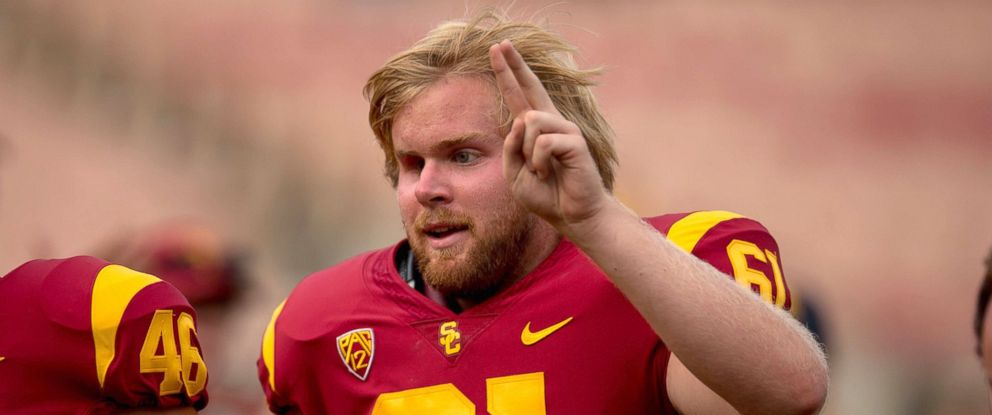 PHOTO: USC long snapper Jake Olson, who has been blind since the age of 12, runs off the field with teammate Wyatt Schmidt after he snapped an extra point attempt during a game between the W. Michigan Broncos vs USC Trojans in Los Angeles.