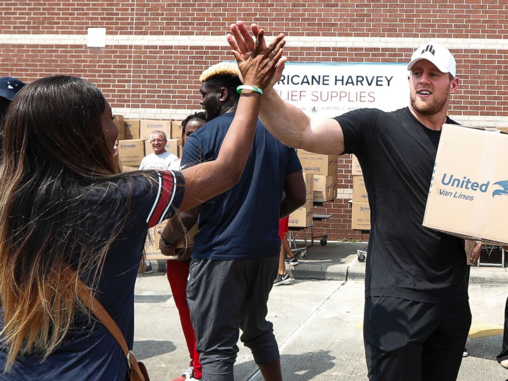 PHOTO: Anna Ucheomumu high fives Houston Texans defensive end J.J. Watt after loading a car with relief supplies for people impacted by Hurricane Harvey on Sept. 3, 2017, in Houston.