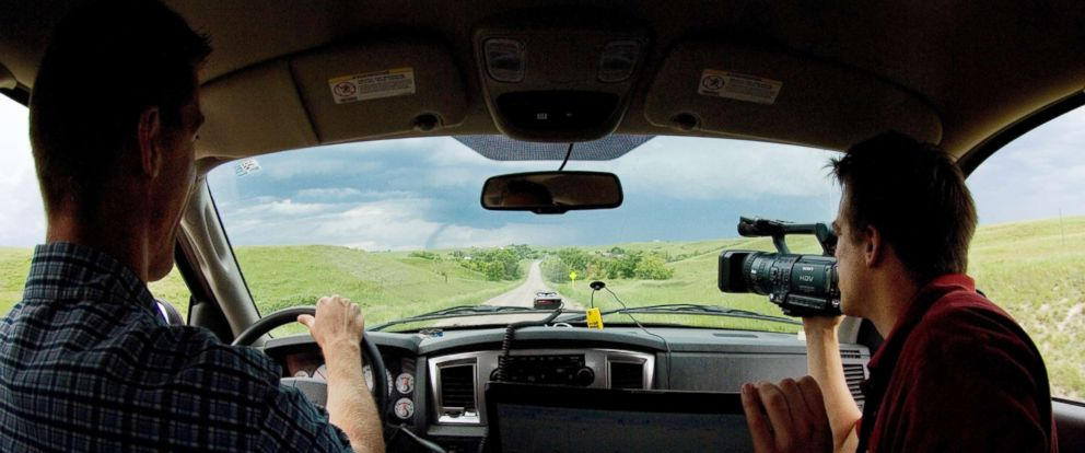 PHOTO: Storm chaser Reed Timmer videotapes a tornado to the left of the road as chase partner Joel Taylor drives in western South Dakota in this undated photo.