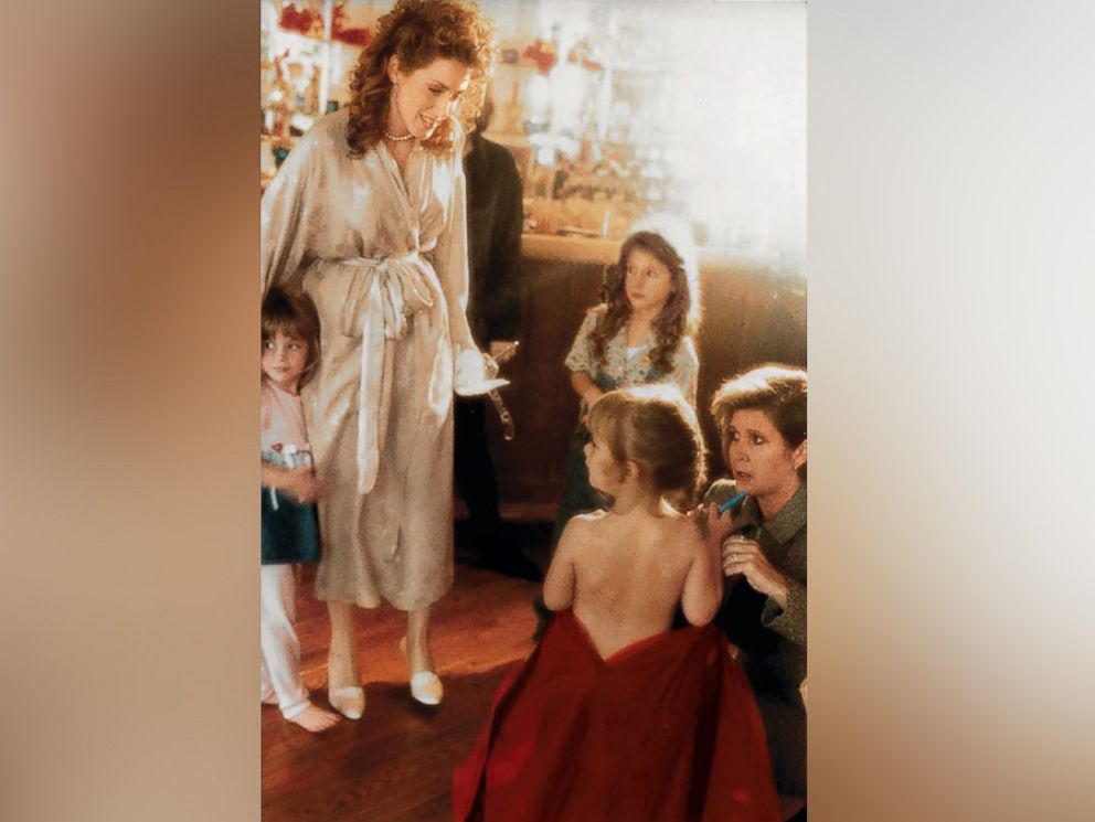 PHOTO: Joely Fisher watches as Carrie Fisher, kneeling, helps dress her daughter, Billie Lourd.