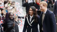 PHOTO: Meghan Markle and Britains Prince Harry are greeted by flag waving school children as they arrive to take part in an event for young women as part of International Womens Day in Birmingham, central England, March 8, 2018.
