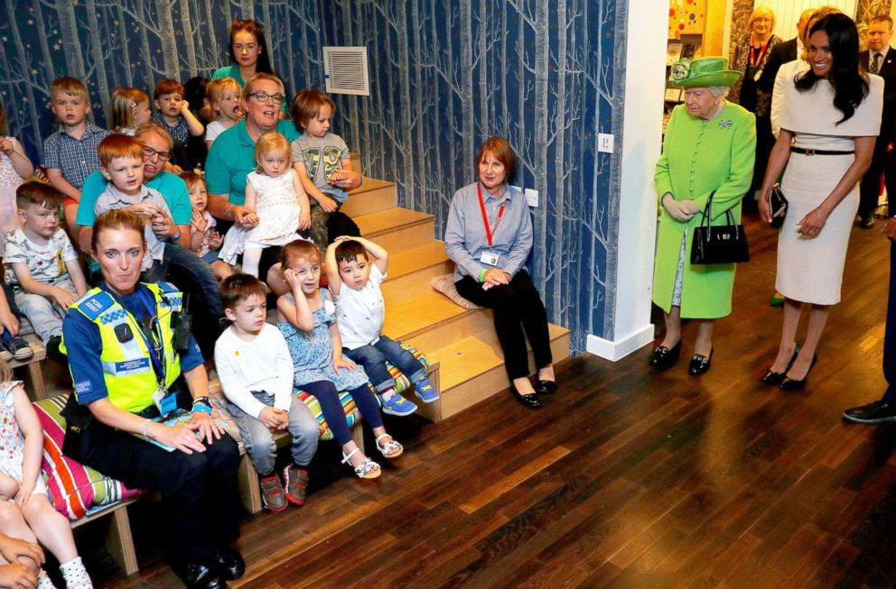 PHOTO: Children sit as Queen Elizabeth II and Meghan, Duchess of Sussex arrive for their visit to the Storyhouse, June 14, 2018, in Chester, England.
