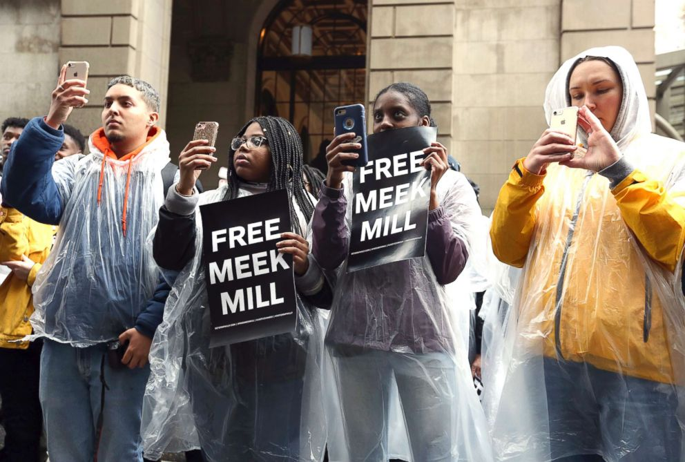 PHOTO: Protesters uses their phones and listen to a speaker in front of a courthouse during a hearing for rapper Meek Mill, April 16, 2018 in Philadelphia.