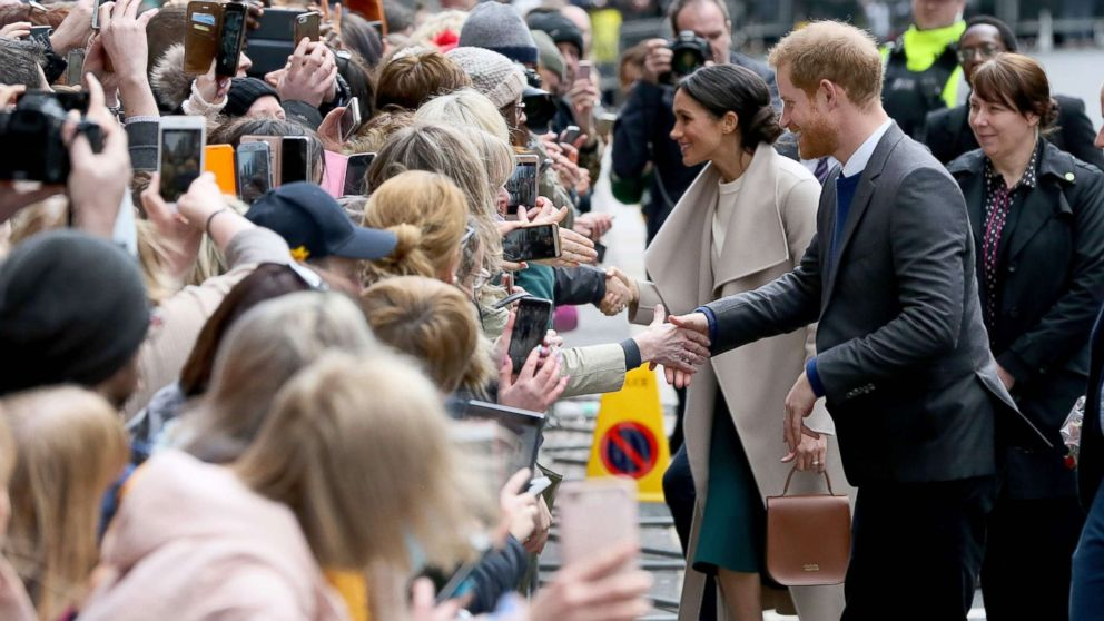 Britain's Prince Harry and his fiancee, Meghan Markle, greet well-wishers after a visit at the historic building, The Crown Liquor Saloon in Belfast, March 23, 2018, where they will learn of the pub's heritage from members of the National Trust.