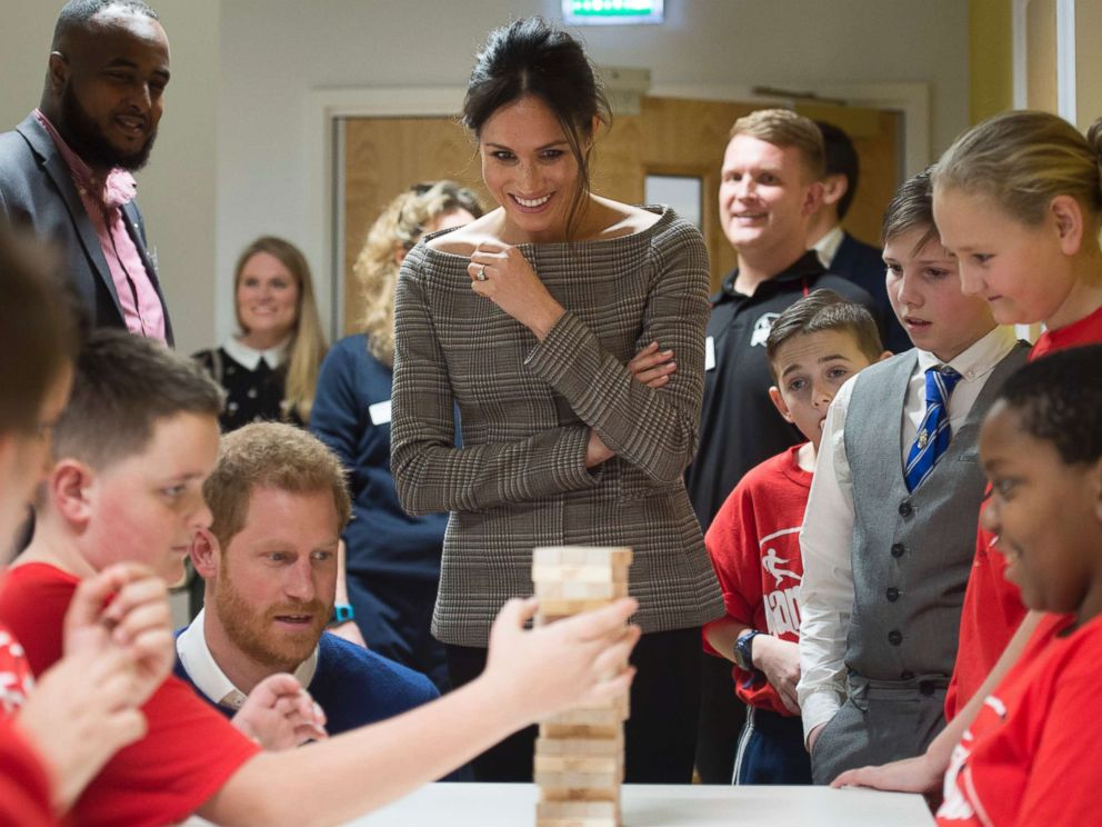 PHOTO: Britains Prince Harry and Meghan Markle reacts as they watch a game of Jenga, during a visit to Star Hub, a community and leisure center in Cardiff, Wales, Jan. 18, 2018.