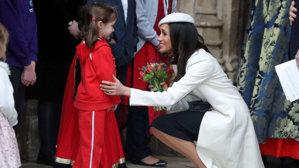 Actress Meghan Markle, fiancee of Britain's Prince Harry, receives a posy of flowers from a young girl after attending a Commonwealth Day Service at Westminster Abbey in central London, March 12, 2018.