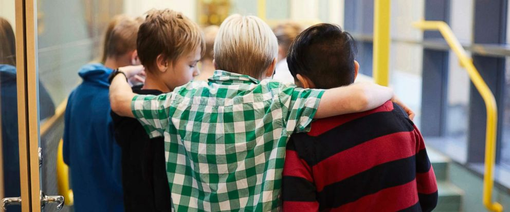PHOTO: Middle-school aged boys stand in a hallway in an undated stock photo.