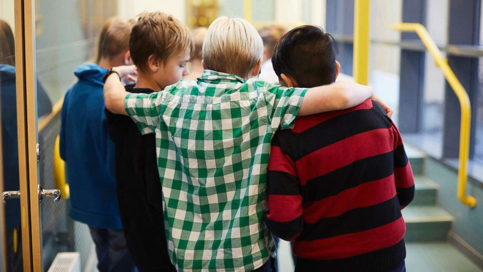Middle-school aged boys stand in a hallway in an undated stock photo.
