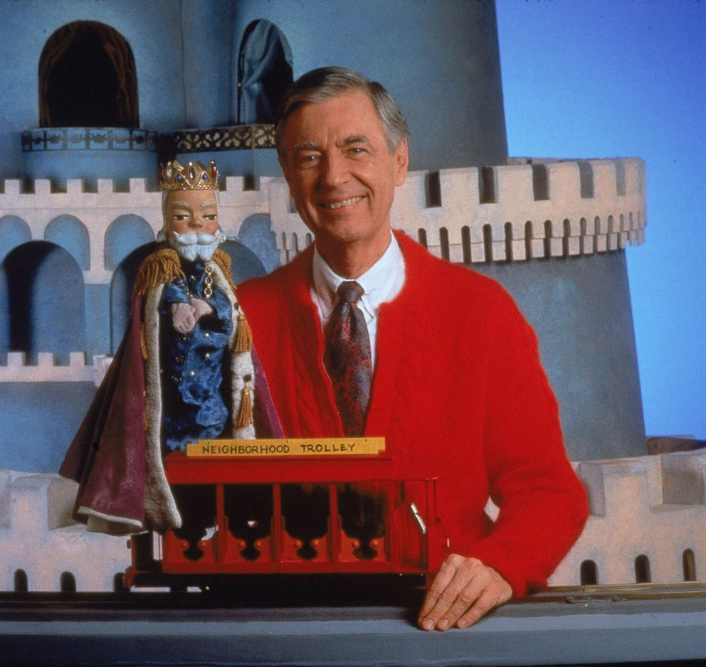 PHOTO: Fred Rogers smiles while posing with a toy trolley on the set of his television show Mister Rogers Neighborhood.