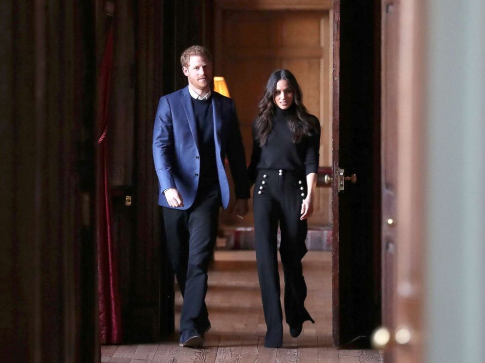 PHOTO: Britains Prince Harry and his fiance actress Meghan Markle walk through the corridors of the Palace of Holyroodhouse on their way to a reception for young people in Edinburgh, during their visit to Scotland, Feb. 13, 2018.