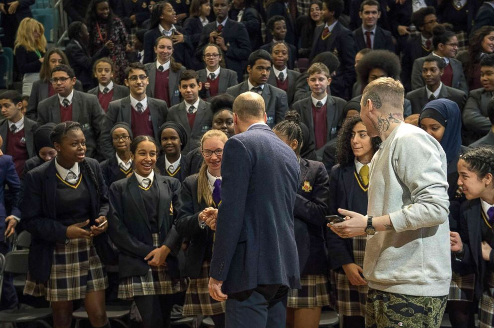 PHOTO: Britains Prince William, accompanied by rapper Stephen Manderson, interacts with students taking part in an assembly on cyber-bullying and its effect on young peoples mental health, during their visit to Burlington Academy, London, Feb. 8, 2018.
