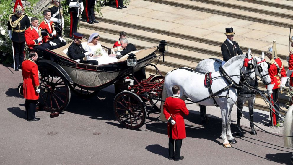 Prince Harry, Duke of Sussex and his wife Meghan, Duchess of Sussex get into the carriage after their wedding ceremony at St George's Chapel, Windsor Castle, in Windsor, May 19, 2018 to start their wedding procession.