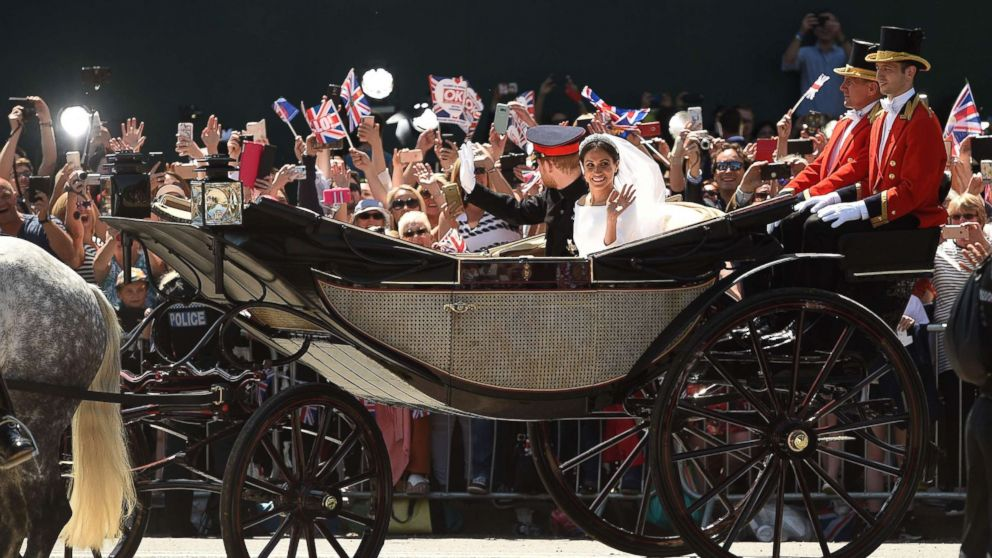 Prince Harry, Duke of Sussex and his wife Meghan, Duchess of Sussex wave from the carriage during their carriage procession on the Long Walk as they head back towards Windsor Castle in Windsor, England, May 19, 2018, after their wedding ceremony.