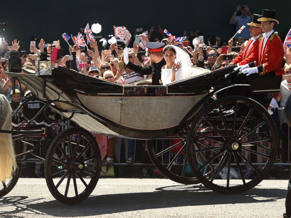 PHOTO: Prince Harry, Duke of Sussex and his wife Meghan, Duchess of Sussex wave from the carriage during their carriage procession on the Long Walk as they head back towards Windsor Castle in Windsor, England, May 19, 2018, after their wedding ceremony.