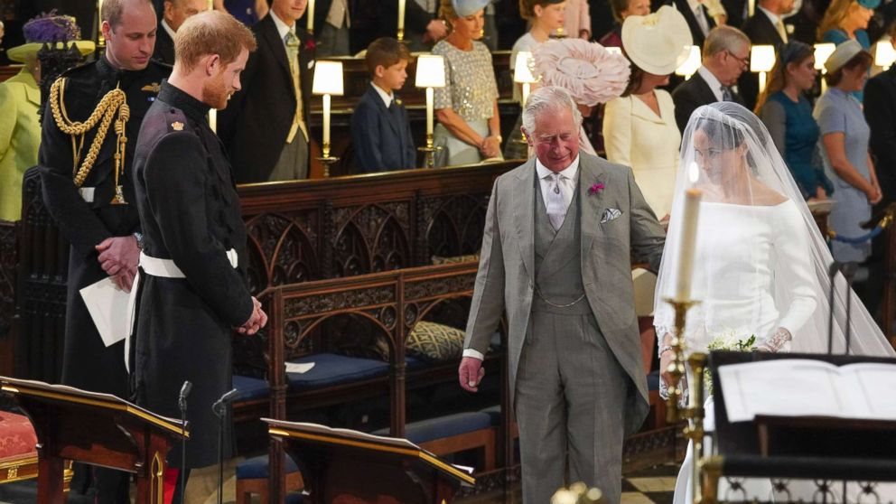 Prince Harry looks at his bride, Meghan Markle, as she arrives accompanied by Charles, the Prince of Wales, in St George's Chapel at Windsor Castle for their wedding, May 19, 2018.