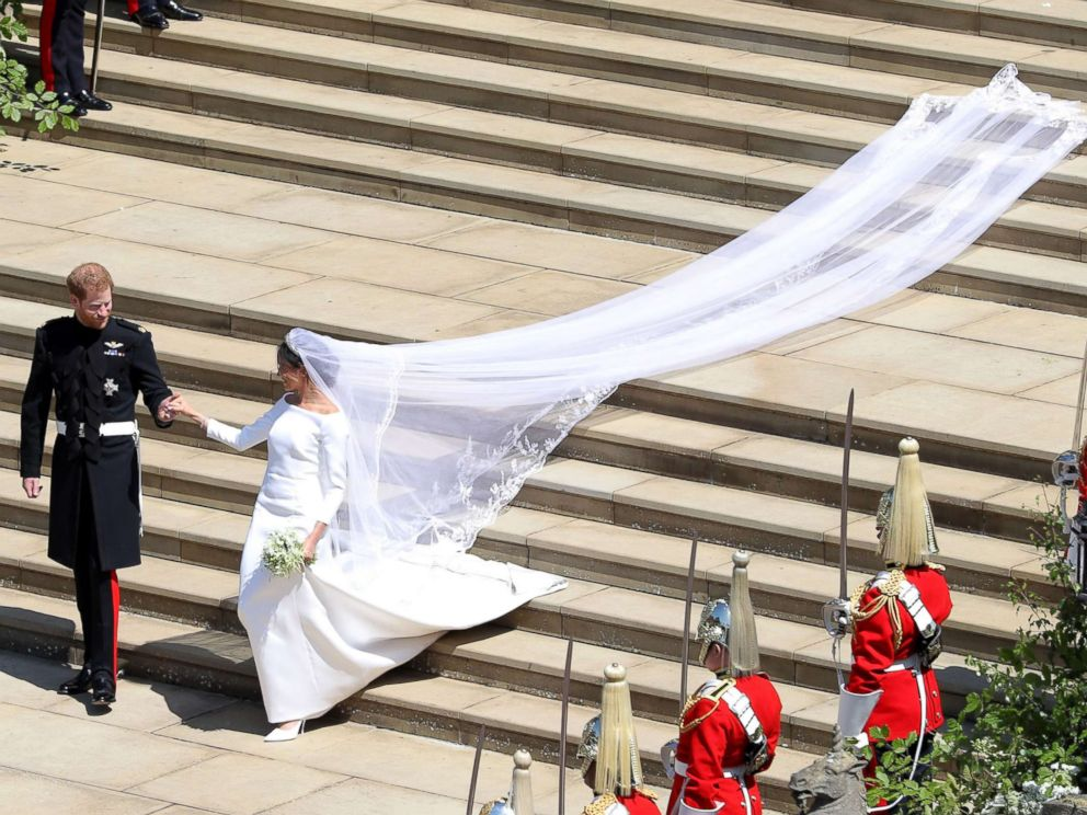 PHOTO: Prince Harry, Duke of Sussex and his wife Meghan, Duchess of Sussex walk down the west steps of St Georges Chapel, Windsor Castle, in Windsor, on May 19, 2018 after their wedding ceremony.
