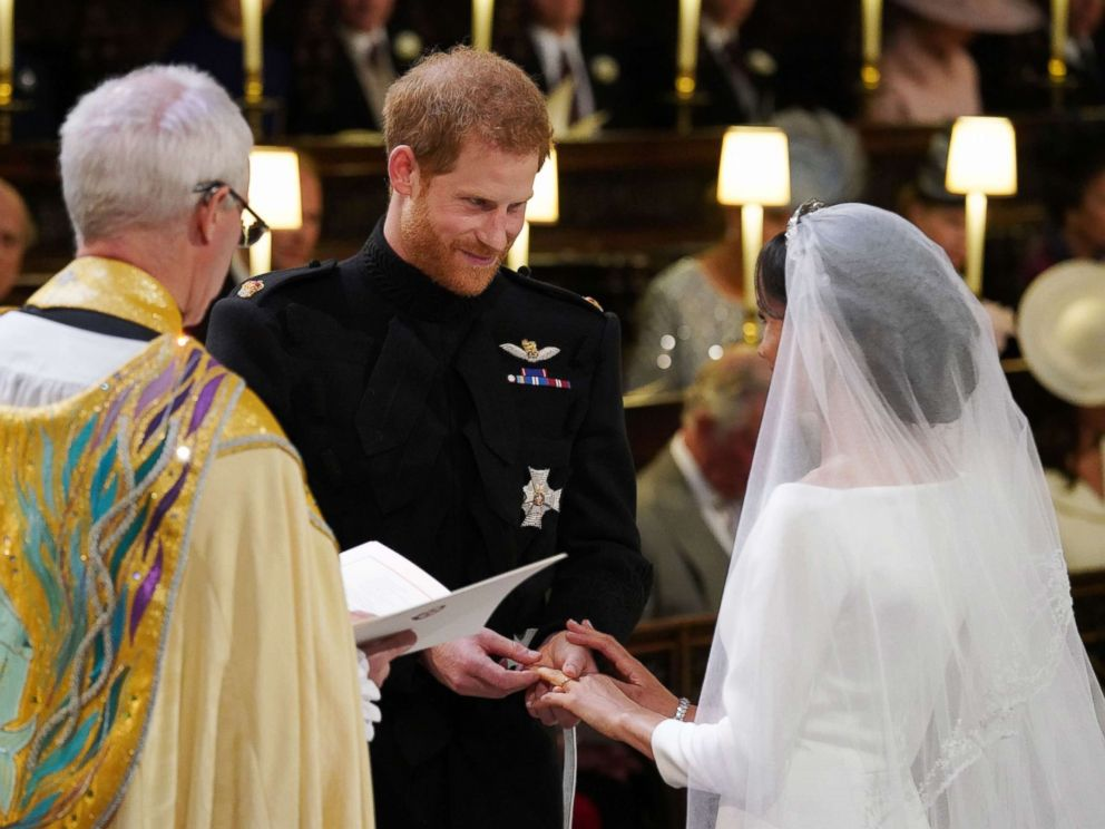 PHOTO: Prince Harry, Duke of Sussex, places the wedding ring on Meghan Markle during their wedding ceremony in St Georges Chapel, Windsor Castle, in Windsor, on May 19, 2018.