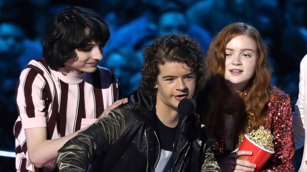 """In this Saturday, June 16, 2018, photo, Finn Wolfhard, from left, Gaten Matarazzo and Sadie Sink accept the award for best show for """"Stranger Things"""" at the MTV Movie and TV Awards at the Barker Hangar in Santa Monica, Calif."""