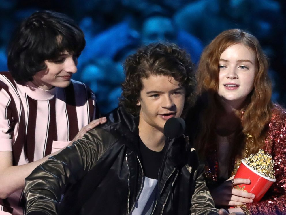In this Saturday, June 16, 2018, photo, Finn Wolfhard, from left, Gaten Matarazzo and Sadie Sink accept the award for best show for Stranger Things at the MTV Movie and TV Awards at the Barker Hangar in Santa Monica, Calif.