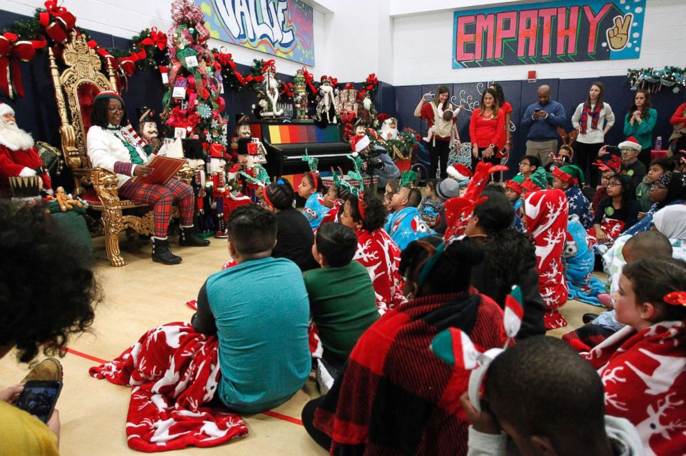 PHOTO: Children gather around to listen as Whoopi Goldberg reads a holiday classic story.