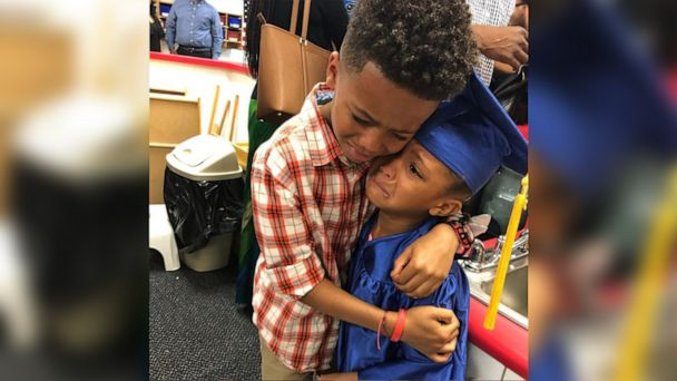 Brother and sister embracing at preschool graduation has hearts exploding