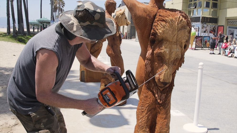 Chainsaw artist Stacy Poitras carves his version of the 7
