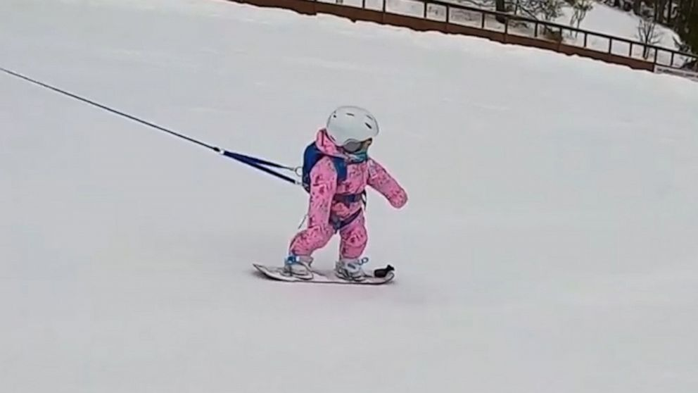 Tethered toddler snowboards like a pro