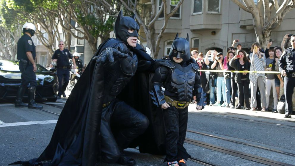 Miles Scott, dressed as Batkid, right, walks with Batman before saving a damsel in distress in San Francisco, Nov. 15, 2013.