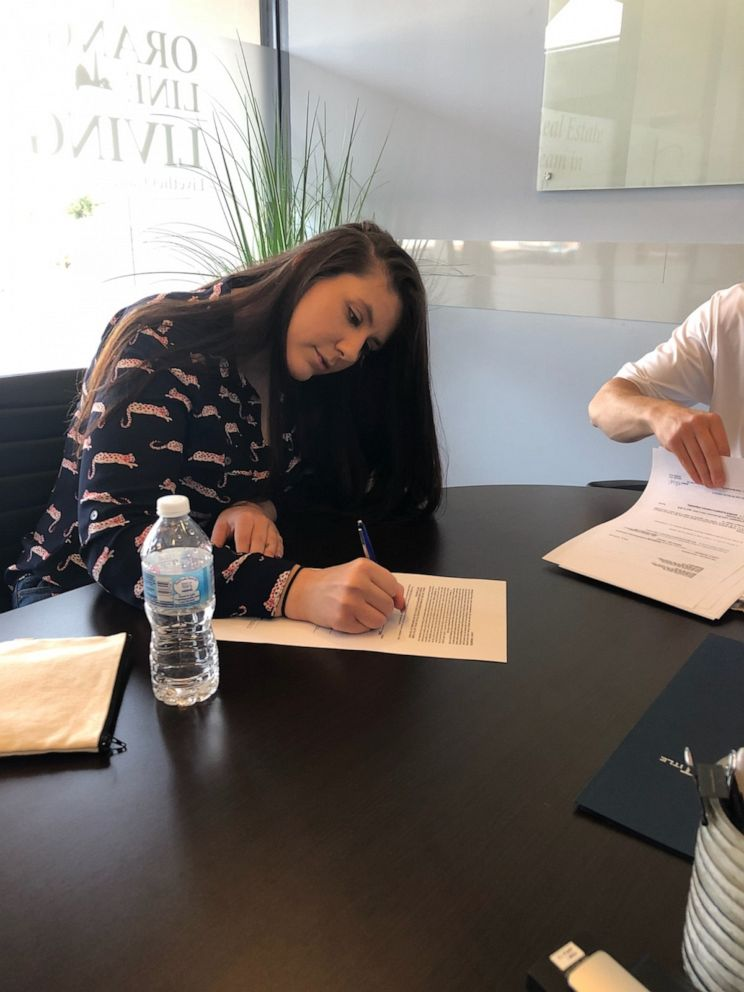 Kassi Yukevich signs paperwork during the home buying process.
