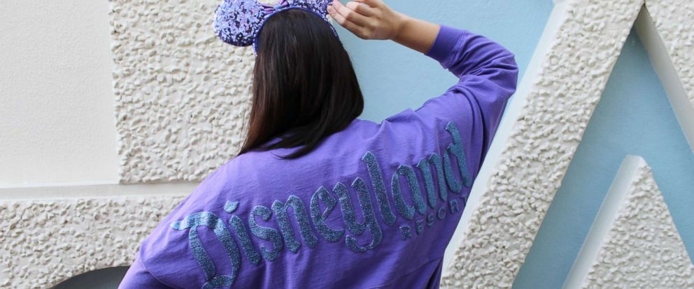"PHOTO: The Potion Purple Spirit Jersey features long sleeves and a shimmery resort logo with a ""D"" icon on the front while the back displays Disneyland Resort in its signature font."