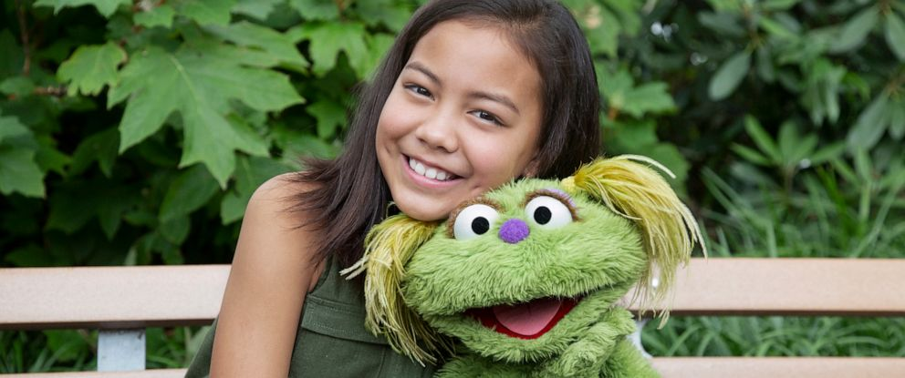 """PHOTO: Salia Woodbury, whose parents are in recovery sits with """"Sesame Street"""" character Karli."""