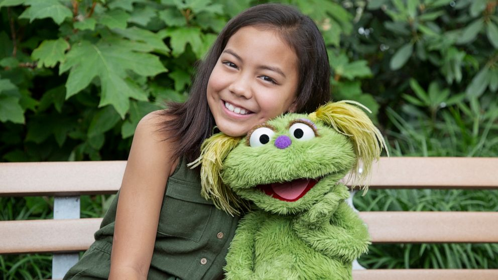 "PHOTO: Salia Woodbury, whose parents are in recovery sits with ""Sesame Street"" character Karli."