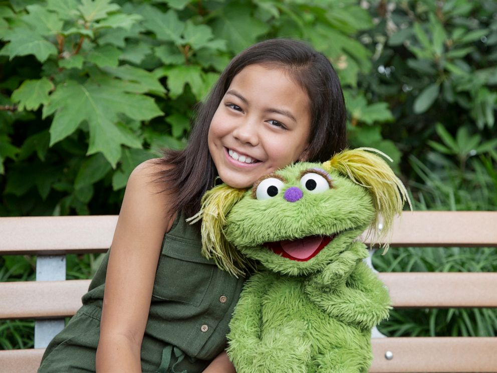 PHOTO: Salia Woodbury, whose parents are in recovery sits with Sesame Street character Karli.