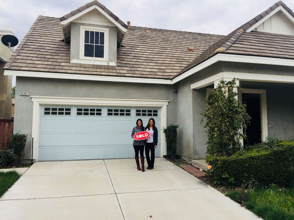Yesenia Cedillo and Jessica Cedillo pose in front of their home.
